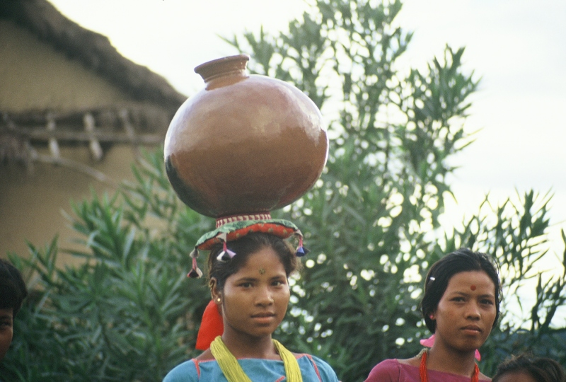 young Tharu girl carries a water jug home on her head