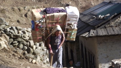 man carrying goods up to Namche Bazaar